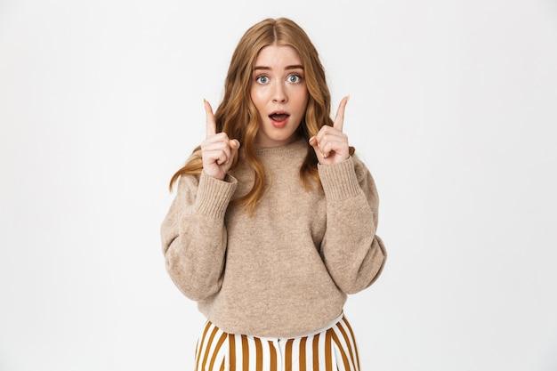긴 금발 곱슬머리에 스웨터를 입은 아름다운 어린 소녀가 흰 벽에 격리되어 복사 공간을 가리키고 있습니다.