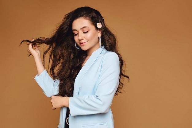 Красивая молодая девушка с длинными вьющимися волосами, украшенная розовым цветком на бежевой стене