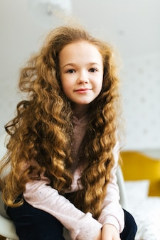 Beautiful young girl with long curly hair smiles and looks into the camera