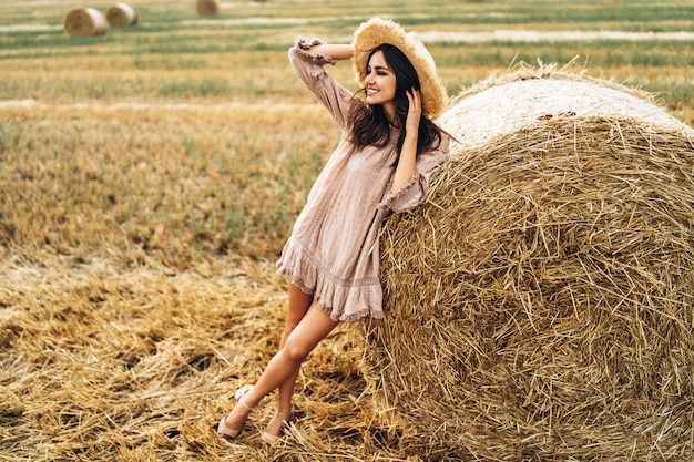 Beautiful young girl with long hair in sunnglasses and straw hat posing on a wheat field near hay bales. happy brunette in summer dress