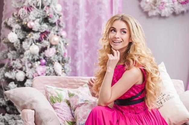 크리스마스 트리의 배경에 핑크 드레스에 긴 물결 모양의 머리를 가진 아름다운 어린 소녀