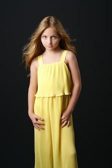 유행 노란색 옷에 느슨한 머리를 가진 아름 다운 젊은 여자