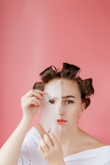Beautiful young girl with a mask and curlers touching her face.