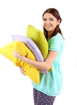 白い表面に分離された枕を持つ美しい少女