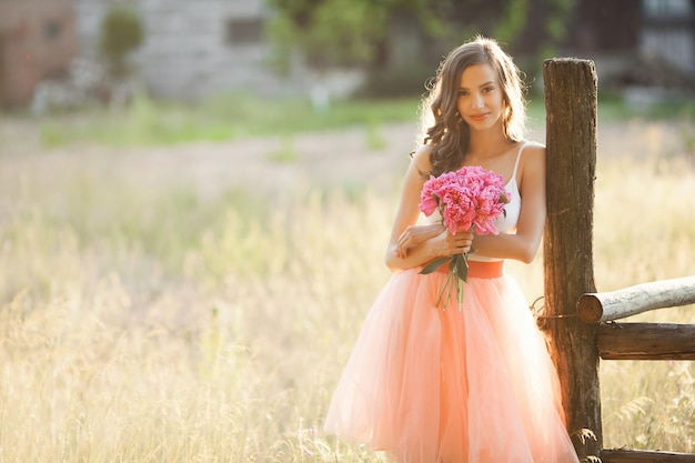 Beautiful young girl with pions on the nature outdoors in the sunshine. pretty woman outside with flowers in the pink skirt