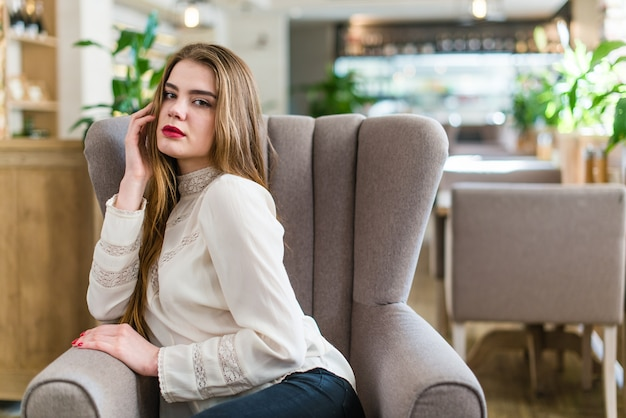 Beautiful young girl with professional makeup and hairstyle sitting in restaurant.
