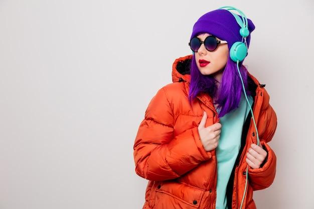 紫色の髪とオレンジ色のジャケットの美しい少女は、ヘッドフォンで音楽を聴きます。