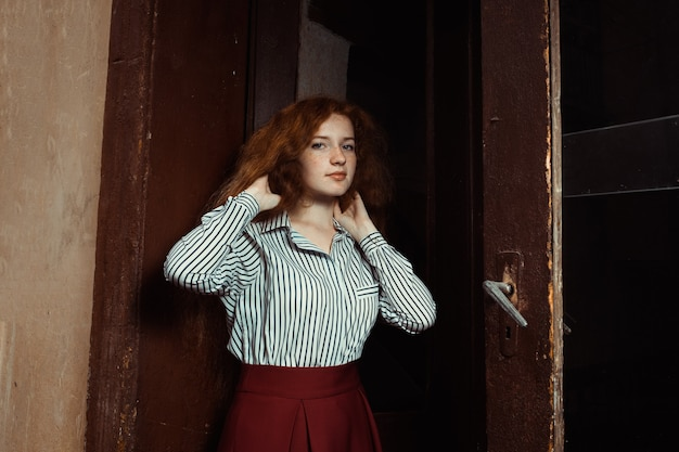 Beautiful young girl with red hair and freckles standing at the old doors