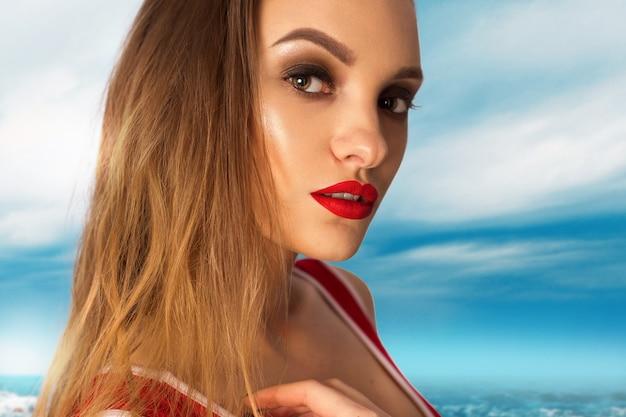 ビーチでカメラを見ている赤い唇を持つ美しい少女