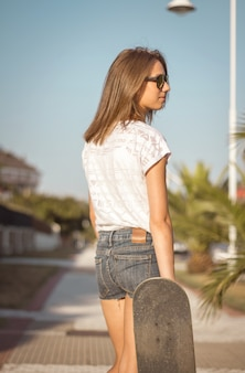 Beautiful young girl with skateboard posing on the street in a sunny summer day