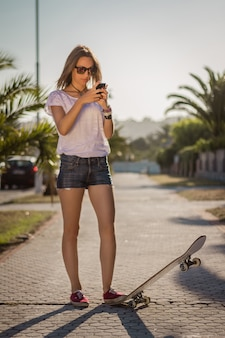 Beautiful young girl with a skateboard using her smartphone outdoor on summer