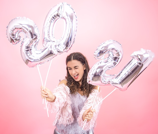 Beautiful young girl with a smile in a festive outfit on a pink studio background holding silver balloons for the new year concept