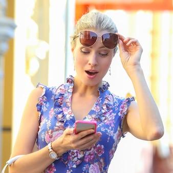깜짝 놀란 아름다운 소녀가 휴대전화를 쳐다본다