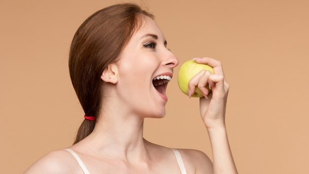 Beautiful young girl with tied on back hair eating tasty apple on lunch. side view of attractive model promoting healthy lifestyle. brunette woman with white teeth holding delicious fruit in her hand.