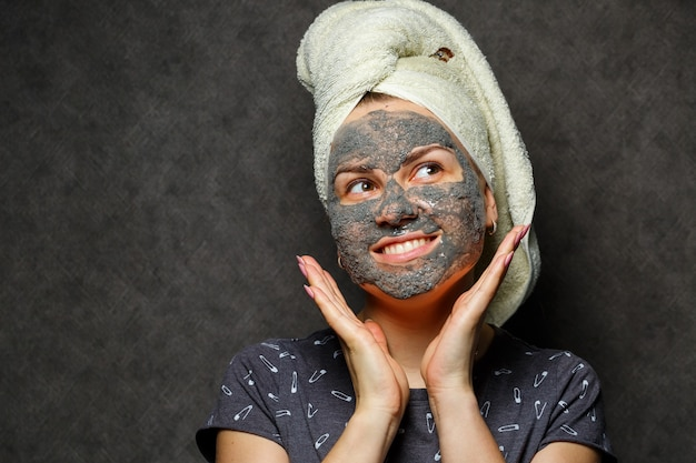 Beautiful young girl with a tonic foam mask on her face and a towel tied with hair