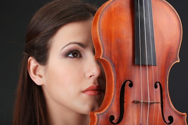 회색 배경에 바이올린을 든 아름다운 소녀