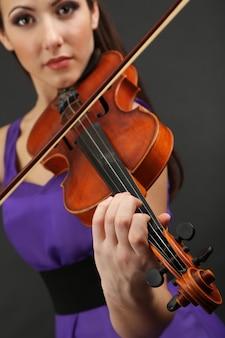 회색 공간에 바이올린과 아름 다운 젊은 여자