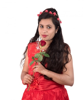 Beautiful young girl or woman holding and posing with red rose flower on white background