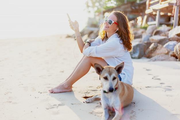 美しい少女の女性は海に沈む夕日の光線でビーチに座って、音楽を聴き、彼女の横に彼女の犬があります