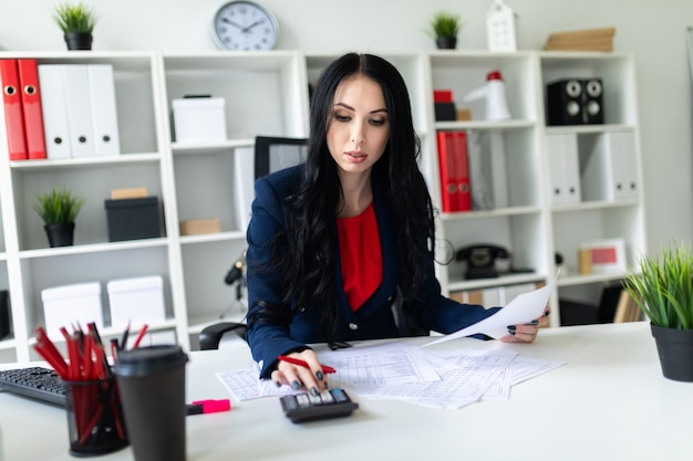 Beautiful young girl working with calculator and documents in the office at the table