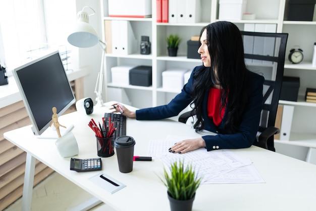 Красивая молодая девушка работает с компьютером и документами в офисе за столом