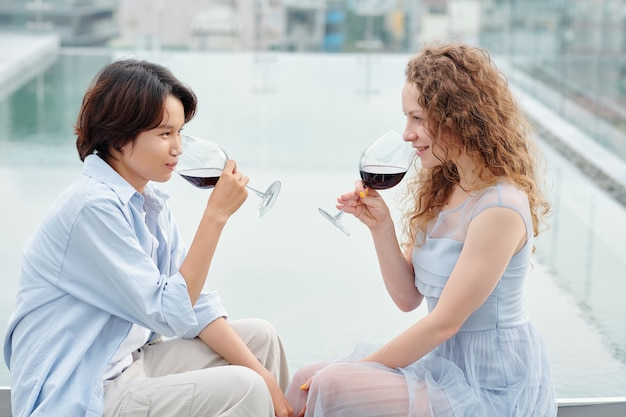 Beautiful young girlfriends drinking red wine and looking at each other when sitting on rooftop
