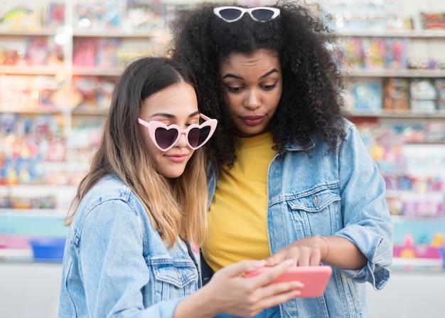 Красивые молодые девушки проверяют мобильный телефон