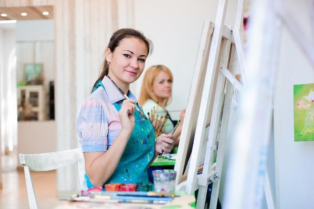 美しい若い女の子がアートレッスンで絵の具を描く