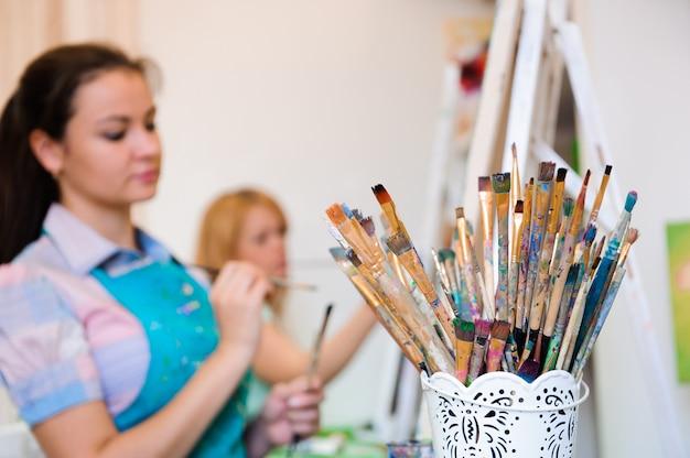 Красивые молодые девушки рисуют картины красками на уроке искусства