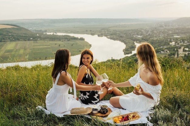 Beautiful young girls girlfriends on a picnic on a summer day.