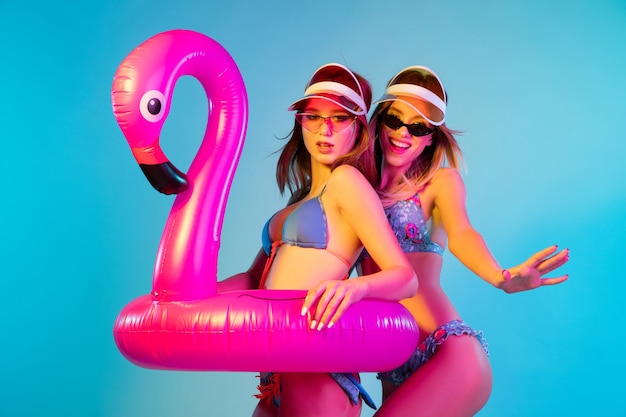 Beautiful young girls' half-length portrait isolated on blue  wall in neon light. women posing in fashionable bodysuit. facial expression, summer, weekend concept. trendy colors.
