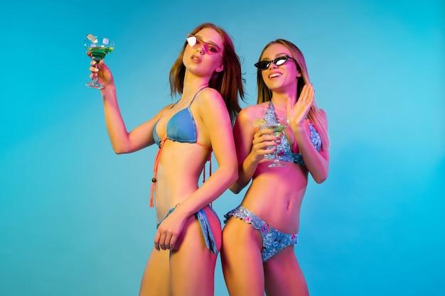 네온 불빛에 블루 스튜디오 배경에 고립 된 아름 다운 젊은 여자의 절반 길이 초상화. 유행 bodysuit에서 포즈를 취하는 여자. 표정, 여름, 주말 개념. 트렌디 한 색상.