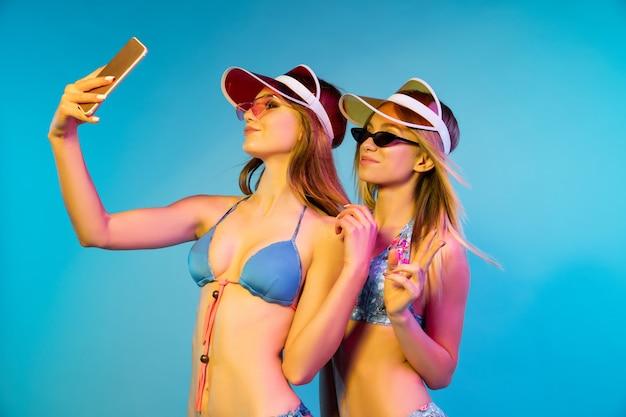 네온 불빛에 파란색 벽에 고립 된 아름 다운 젊은 여자의 절반 길이 초상화. 유행 bodysuit에서 포즈를 취하는 여자. 표정, 여름, 주말 개념. 트렌디 한 색상.