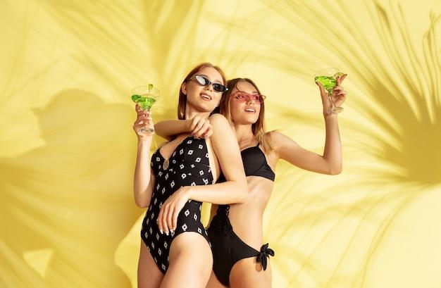 ヤシの影を持つ黄色いスタジオ背景に分離された美しい若い女の子の半身像。ファッショナブルなボディー スーツでポーズをとる女性。表情、夏、週末のコンセプト。トレンドカラー。