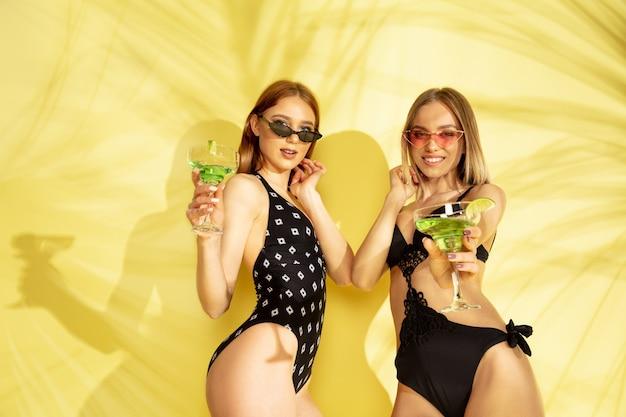 팜 그림자와 노란색 스튜디오 배경에 고립 된 아름 다운 젊은 여자의 절반 길이 초상화. 유행 bodysuit에서 포즈를 취하는 여자. 표정, 여름, 주말 개념. 트렌디 한 색상.