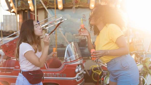 Красивые молодые девушки веселятся в парке развлечений