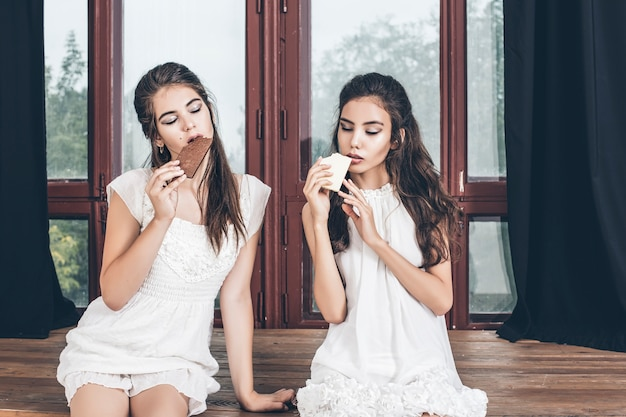 レトロなスタイルで木製の窓にチョコレートと一緒に座っている白いドレスの美しい若い女の子