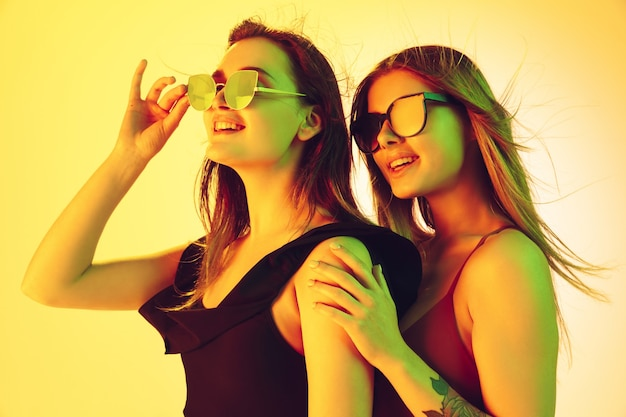ネオンの光の中で黄色のスタジオの背景に分離された美しい若い女の子の肖像画。ファッショナブルなボディスーツの女性。顔の表情、夏、週末、美しさ、リゾートのコンセプト。休暇、若者。