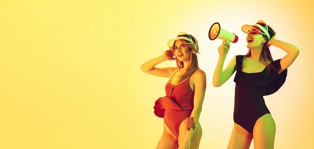 Портрет красивых молодых девушек, изолированные на желтом фоне студии в неоновом свете. женщины в модных боди. выражение лица, лето, выходные, красота, концепция курорта. каникулы, молодость.