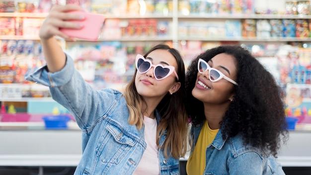 Belle ragazze che prendono insieme un selfie
