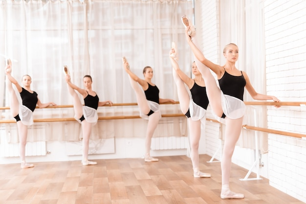 Beautiful young girls train in the hall for ballet.