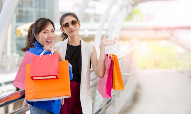 Красивые молодые девушки с красочными сумками на пути к торговому центру