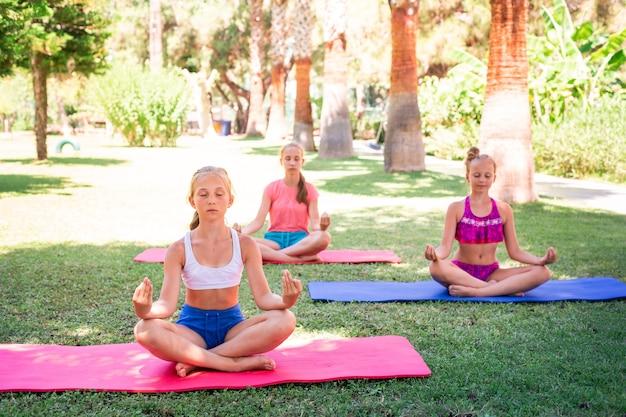 아름다운 어린 소녀들이 운동하고, 운동하고, 리조트에서 야외 요가를 연습합니다. 건강한 라이프 스타일과 피트니스 야외 개념