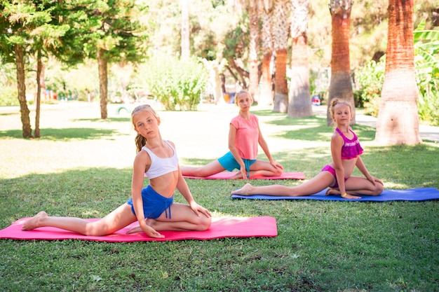Beautiful young girls working out, exercising, practicing yoga outdoor at the resort. healthy lifestyle and fitness outdoor concept