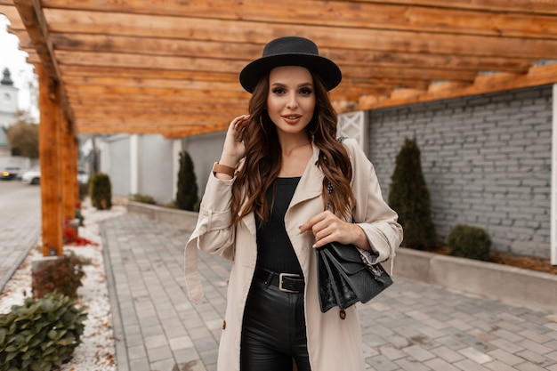 Beautiful young glamorous woman with curly hair in a fashionable hat with a classic beige coat and a leather handbag walks on the street.  feminine elegant style and beauty