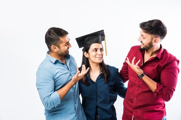 白い壁に卒業式の帽子をかぶっている間、男性の友人との成功を祝う美しい若い大学院インドの女の子の学生