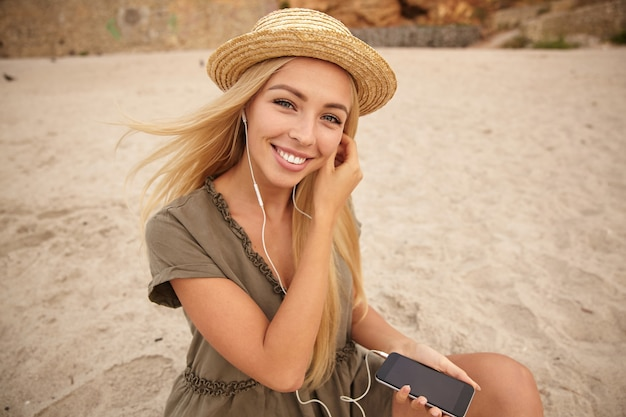 Beautiful young green-eyed blonde woman with natural makeup looking cheerfully at camera with broad smile while inserting earphone in ear, sitting over beach background