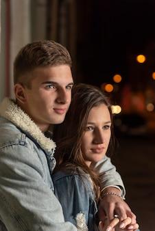 美しい若い男は夜の街の背景に彼の最愛の人を抱きしめます。夜のロマンチックなデートの若いカップル。垂直フレーム。
