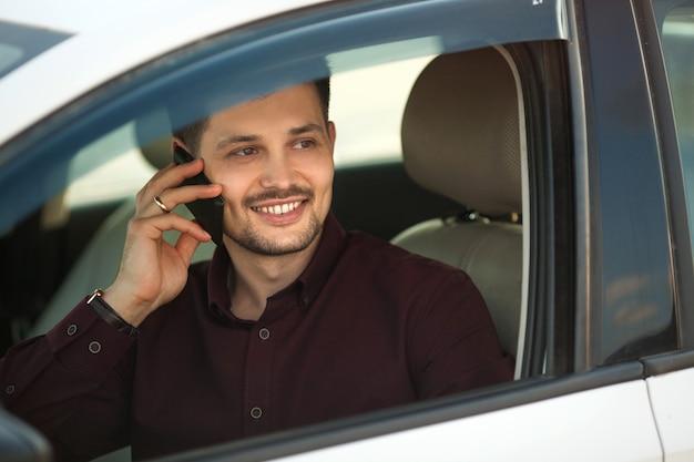 Красивый молодой парень в рубашке сидит в машине и разговаривает по телефону
