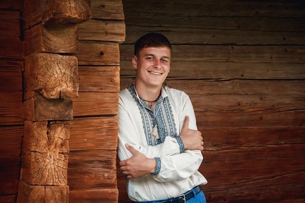 Красивый молодой парень в вышитой рубашке на фоне деревянного дома.